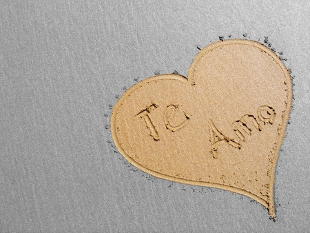 Heart with the words Te Amo drawn in the sand. photo