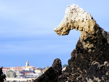 Stone horse called El Caballuco and the town of Noja. Spain.