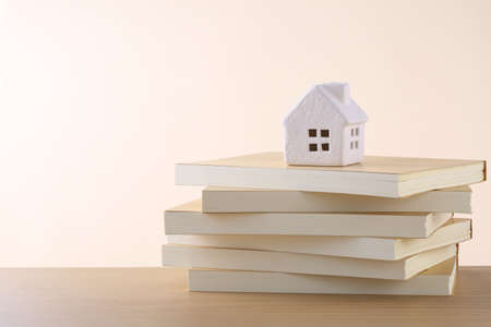 put a model of a house on top of a book