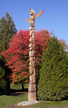 Totem pole in fall in front of red maple tree