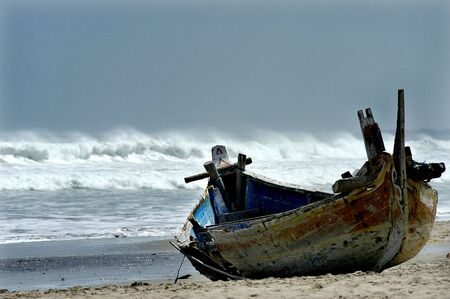 Fishing boat run a ground on the beach on a popular beach in Bali with crashing waves in the back ground.                              Stock Photo