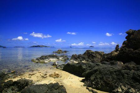 Nave a vela nella schiena a terra con cieli blu in cornice tropicale nelle Figi.