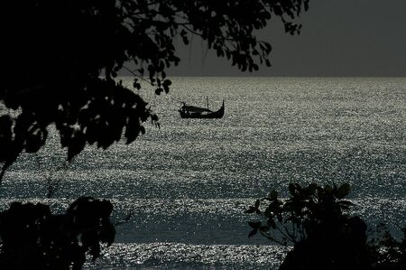 Balinese fishing boat sailing off in the distance silhouetted around the ocean in Bali