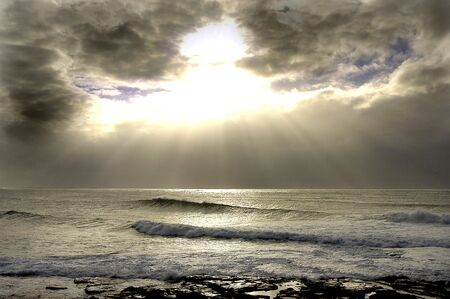 Light breaking thru the clouds with the waves breaking across the reef in Australia.                                 Stock Photo