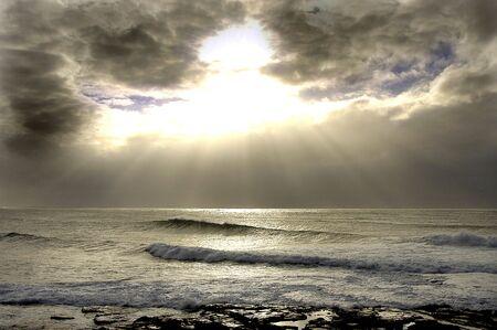 Luce di rottura attraverso le nuvole con le onde di rottura attraverso la barriera corallina, in Australia.                                 Archivio Fotografico