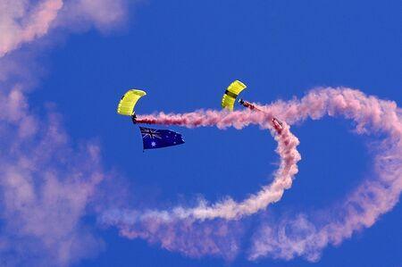 Due Skydivers paracadutismo azienda fumo una bandiera australiana con rosa in Australia Day celebrazioni.  Archivio Fotografico
