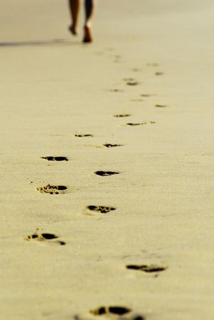 Foot Prints in the Sand as runner leaves them behind on a beach in Australia.