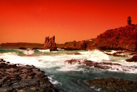 View of Cathedral Rocks in Kiama NSW Australia with Ocean crashing on the rocks.