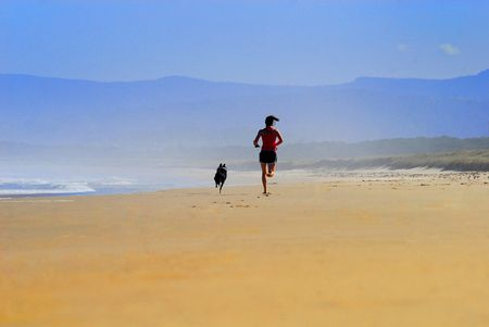 Girl with Dog running along the beach with the mist in the back ground.