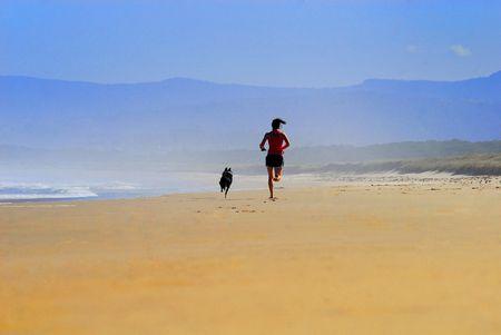 Ragazza con il cane che corrono lungo la spiaggia con la nebbia nella terra posteriore.