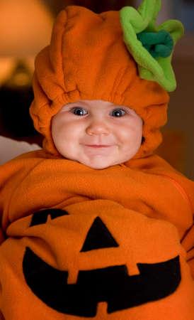 Niña en traje de calabaza de Halloween