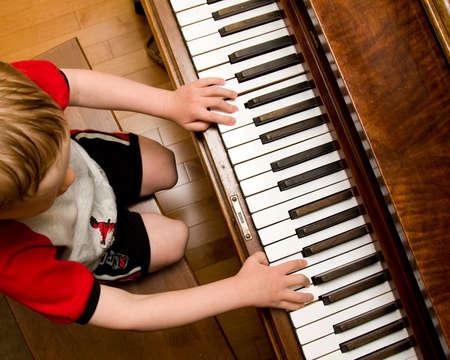 tocando piano: Ni�o aprendiendo a tocar el piano Foto de archivo