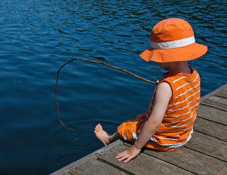 Boy pretending to fish off dock Stock Photo - 10658197