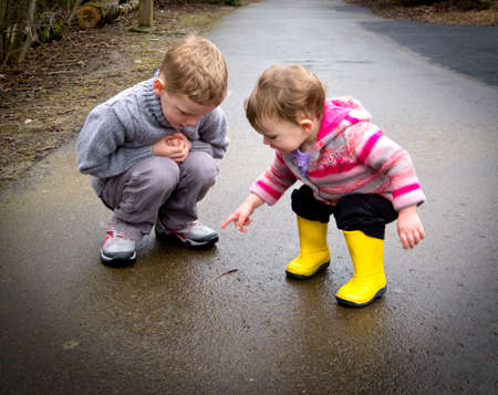 Kids watching worm on rainy day photo
