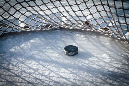 Hockey net with puck in goal photo