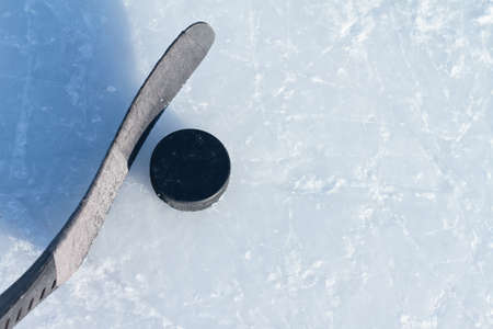 rink: hockey stick and puck on ice