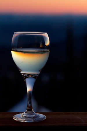 white wine glass: White wine glass at sunset Stock Photo