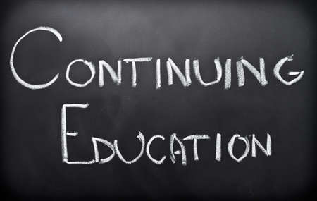 continuing education: Continuing education written on classroom blackboard