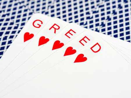 Greed in card hand Imagens