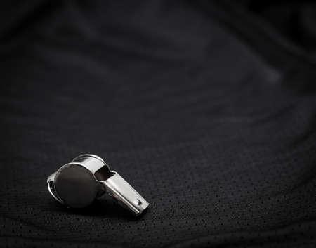 Referee whistle on black background
