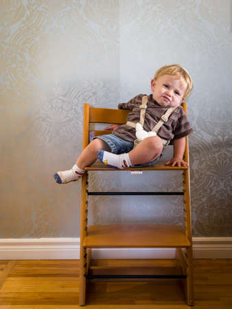highchair: Bored baby in highchair Stock Photo