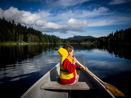 Child canoeing on lake photo