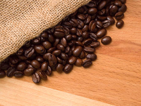sackcloth: Coffee beans in burlap sack on wood Stock Photo