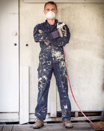 messy: Handyman with paint sprayer Stock Photo