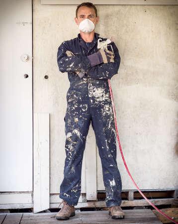 Handyman with paint sprayer Stock Photo