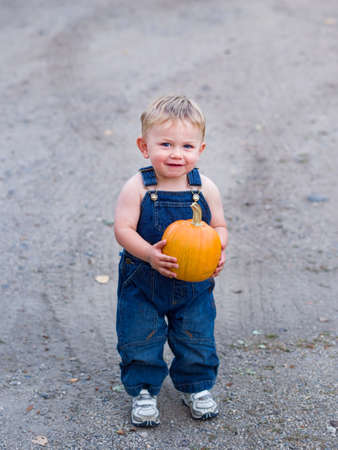 Happy boy holding pumpkin photo