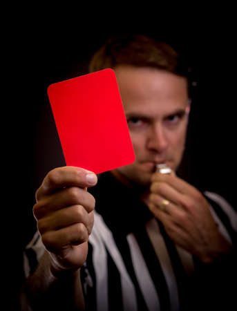 Referee holding red card for foul concept