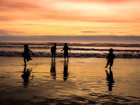 ocean waves: Kids playing on beach Stock Photo
