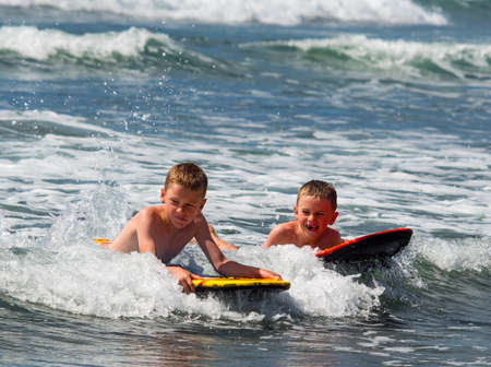 Two boys playing in surf photo