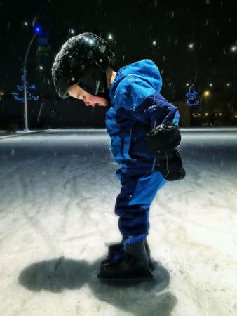 Boy ice skating on outdoor ice rink