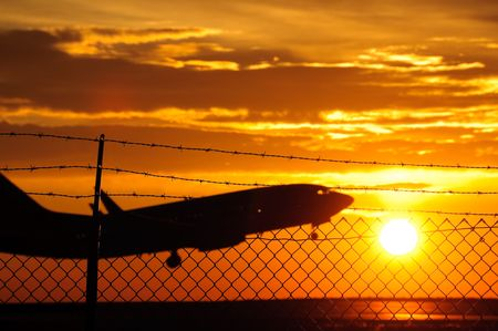 Silhouette of a commercial plane taking off behind a security fence at Denver international airport. Stock Photo