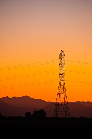 High tension power line tower sillouetted at sunset.