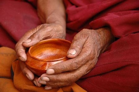 meditation pray religion: Hands of a Tibetan monk holding a wooden tea cup.  Lama Yuru, Ladakh, India