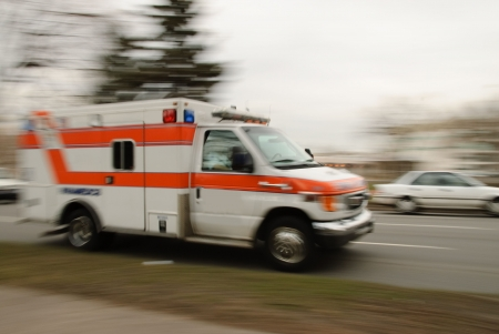 A motion blur of an ambulance driving down a street.