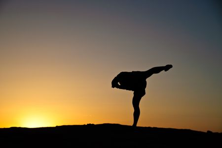 Silhouette of a man doing yoga as the sunsets.