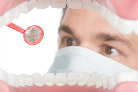 Dentist inspecting teeth inside a mouth Stock Photo