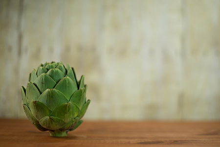 A ripe green artichoke sitting on a wood