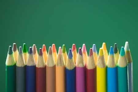 Lijn van kleurpotloden voor een groen schoolbord.