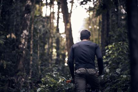 Man with machete hiking through the jungle
