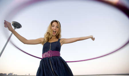 A young blond woman, dressed in a blue sun dress, enjoys her plastic hoop