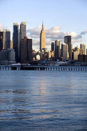 Midtown Manhattan, reflecting the setting sun, Chelsea and the Hudson River show in this skyline of New York City.