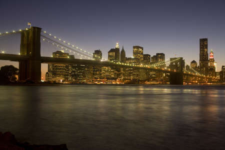 The iconic Brooklyn Bridge and downtown New York City skyline at dusk.