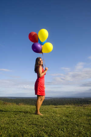 Late twenties woman in red dress stands on a hilltop while holding colorful balloons