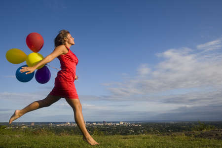 Letting out her inner child, she jumps with balloons through a meadow far from the city below Stock Photo - 10656142