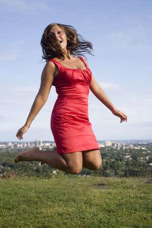 Verhuur van haar innerlijke kind, springt ze op een heuveltop weiland ver van de stad hieronder