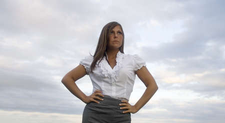 Attractive business woman looks off into the distance, assuming a Super Woman pose, letting you know that she is competent, capable and in charge. She is the champion of your cause, the hope for your company as storm clouds gather!